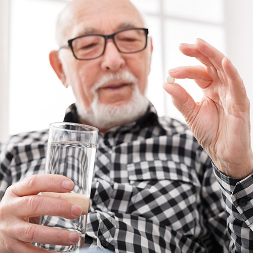 man holding pill and glass of water