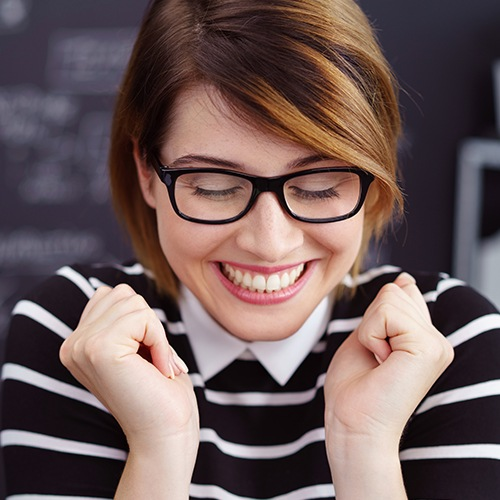 Woman with glasses smiling big