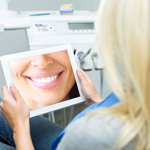 Woman looking at smile on tablet